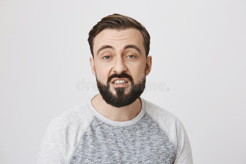 表现出有胡子的欧洲的人画象与张的嘴和厌烦的表示的憎恶,站立在灰色 免版税图库摄影