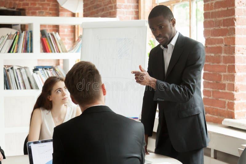 表现粗鲁在简报meetin期间的非裔美国人的雇员 免版税库存照片