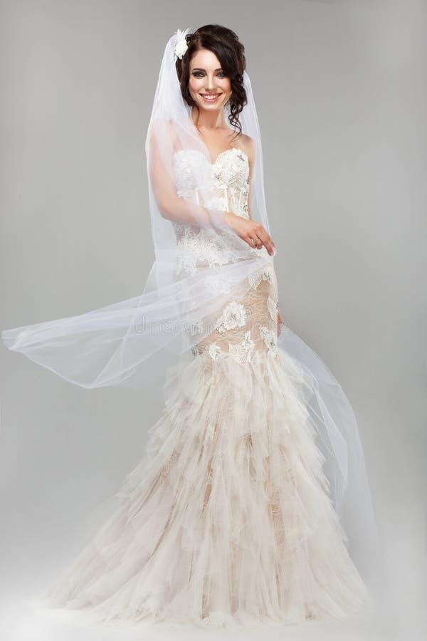 表示。正面情感。有风婚礼礼服的华美的微笑的新娘 库存照片