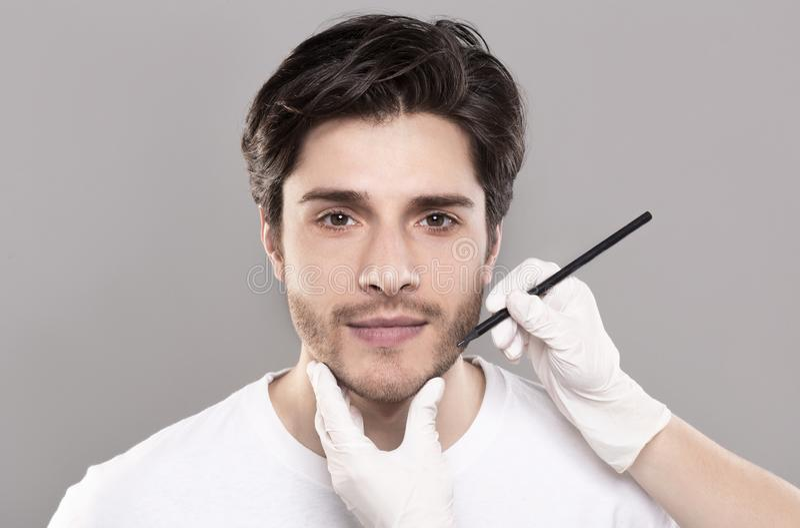 表示男性面孔的美容师手在秀丽操作前 免版税库存图片