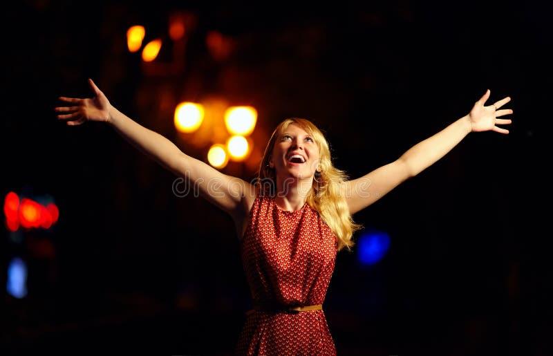 表示美丽的女孩高兴,夜城市 免版税库存图片