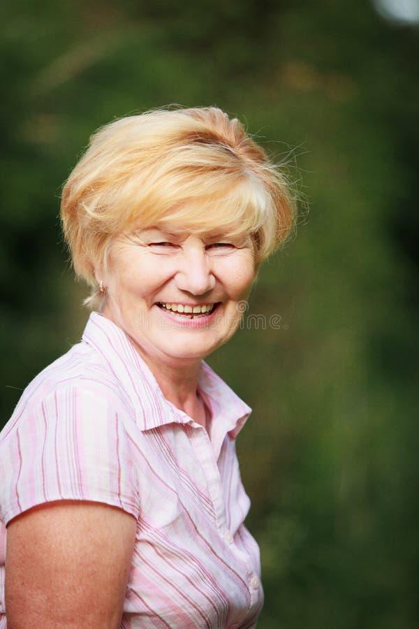 表示&正面情感。有放光的暴牙的微笑和蔼可亲的老妇人 图库摄影
