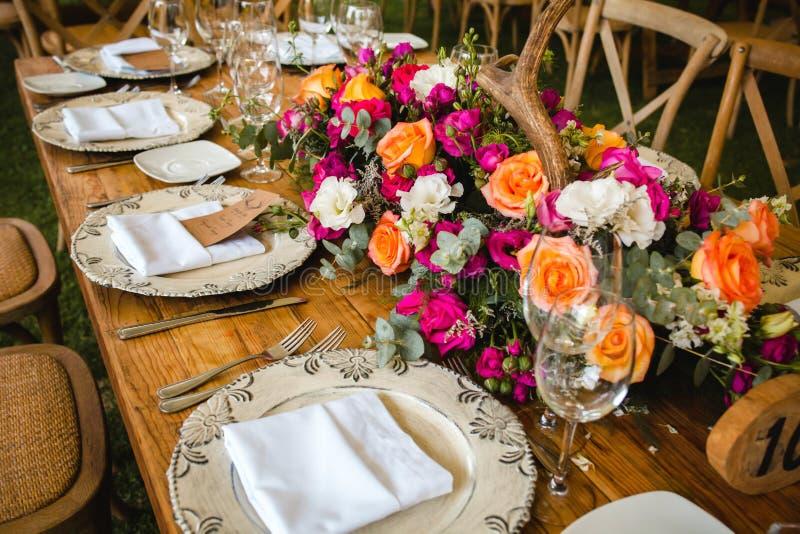 表设定,婚姻客人桌、招待会布局在pantone居住的珊瑚和鹿垫铁土气样式 库存照片