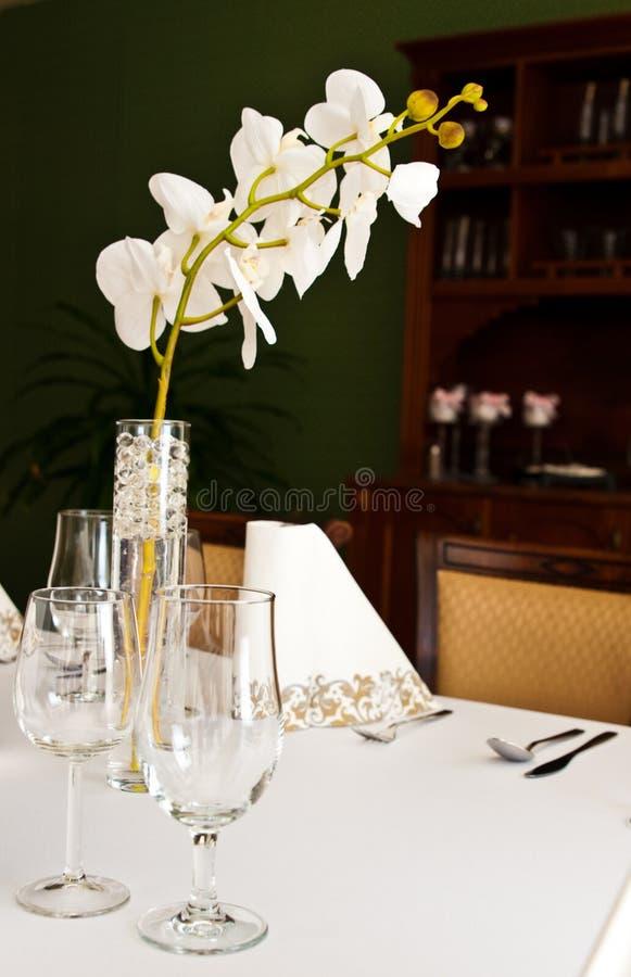 表设置在有兰花花的餐馆 免版税库存图片