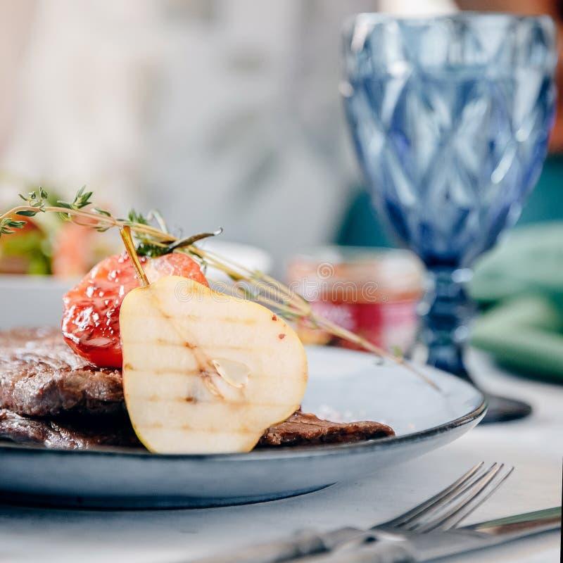 表设置在餐馆是与梨和蕃茄装饰的新鲜的肉牛排 利器和酒杯 库存图片
