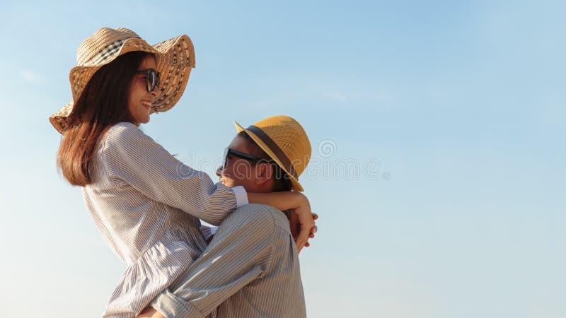 表达亚洲的夫妇他们的感觉,当站立在海滩,年轻夫妇时在天空蔚蓝拥抱 库存图片
