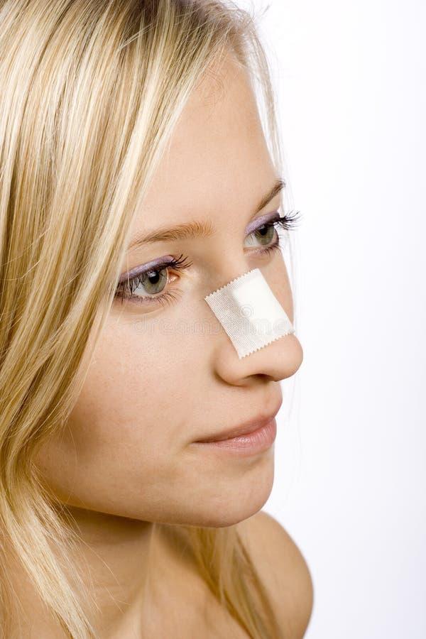表面停留妇女年轻人的鼻子膏药 免版税图库摄影