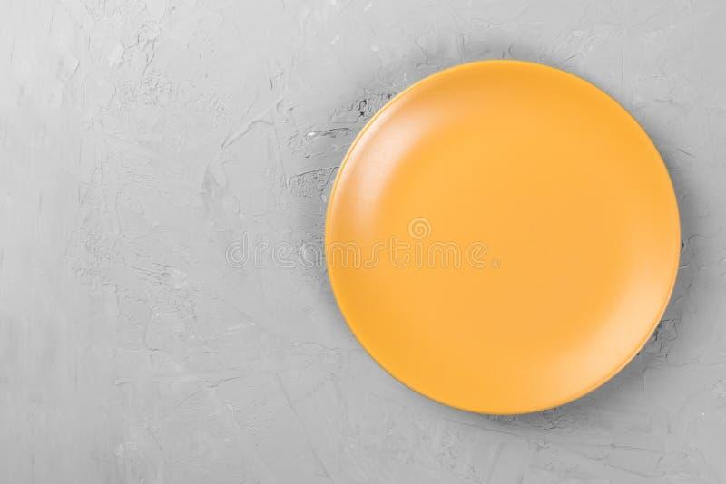 表面无光泽的在黑暗的水泥背景空间的回合空的橙色板材顶视图您的设计 免版税库存照片
