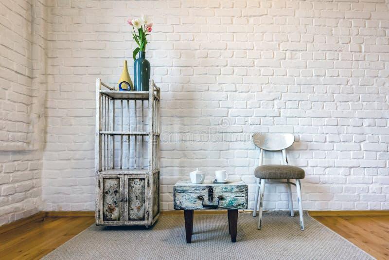 表,椅子,在一个白色砖墙的背景的架子在葡萄酒顶楼内部的 免版税图库摄影