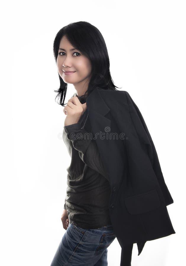 黑衬衣、夹克和蓝色牛仔裤的愉快的妇女 免版税库存图片