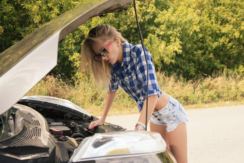 衬衣和短裤的美丽的亭亭玉立的女孩在开放汽车敞篷看 库存图片