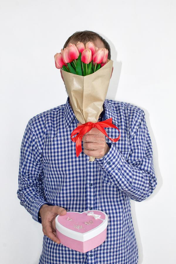 衬衣的一个人拿着在他的面孔前面的郁金香花并且提供在白色背景的一个心形的箱子 免版税库存照片
