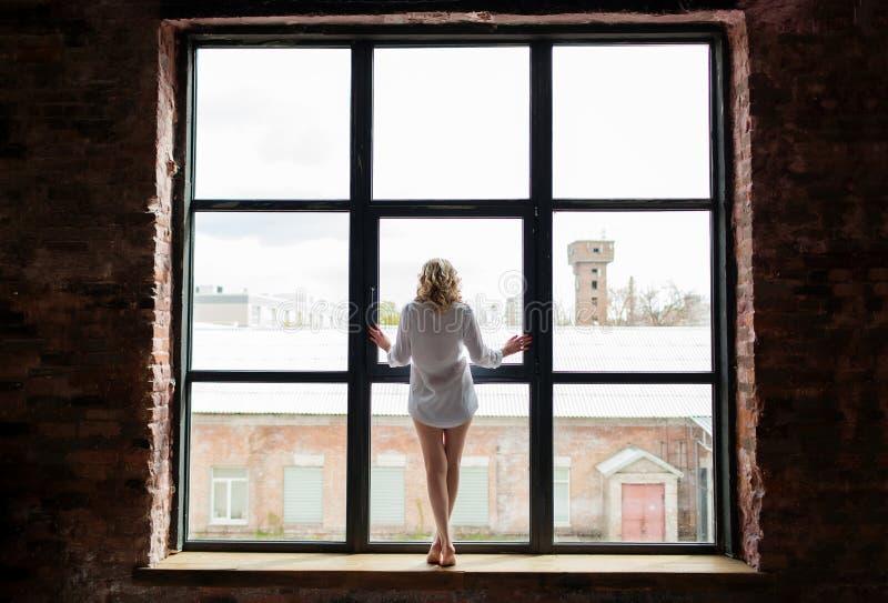 衬衣的一名美丽的妇女在窗台站立并且看窗口 图库摄影