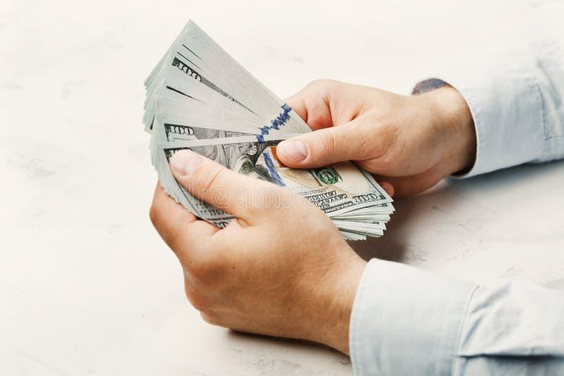 衬衣的人在他的手上的拿着美元金钱 经济,挽救,贸易,薪金和捐赠概念 免版税库存照片
