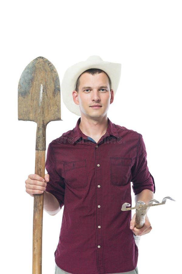 衬衣的农夫拿着为土壤处理的工具 免版税库存图片