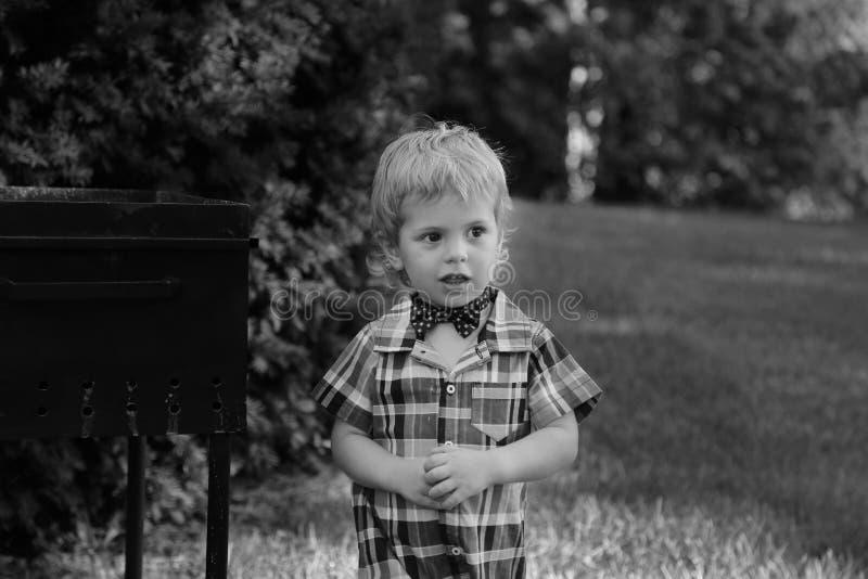衬衣的小男孩和在公园黑色&白色的蝶形领结 库存照片