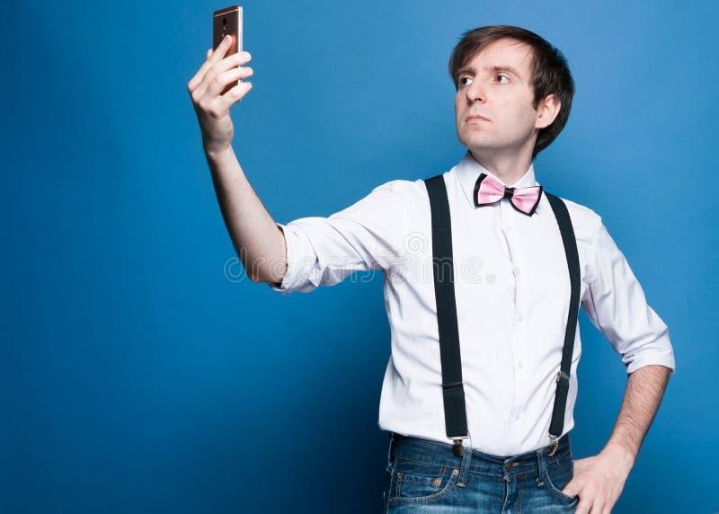 衬衣的帅哥有滚动的站立和采取selfie的袖子和黑悬挂装置 免版税库存照片