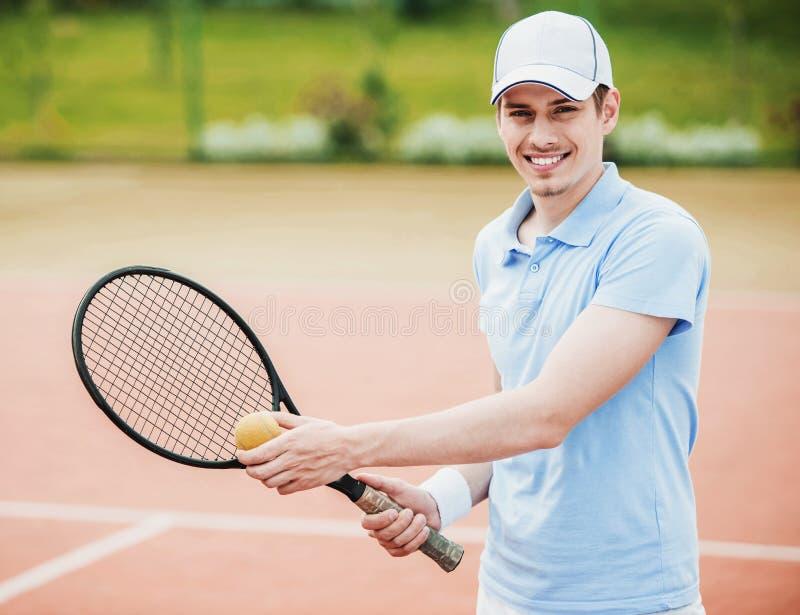 衬衣的年轻人准备服务在网球场 免版税库存图片