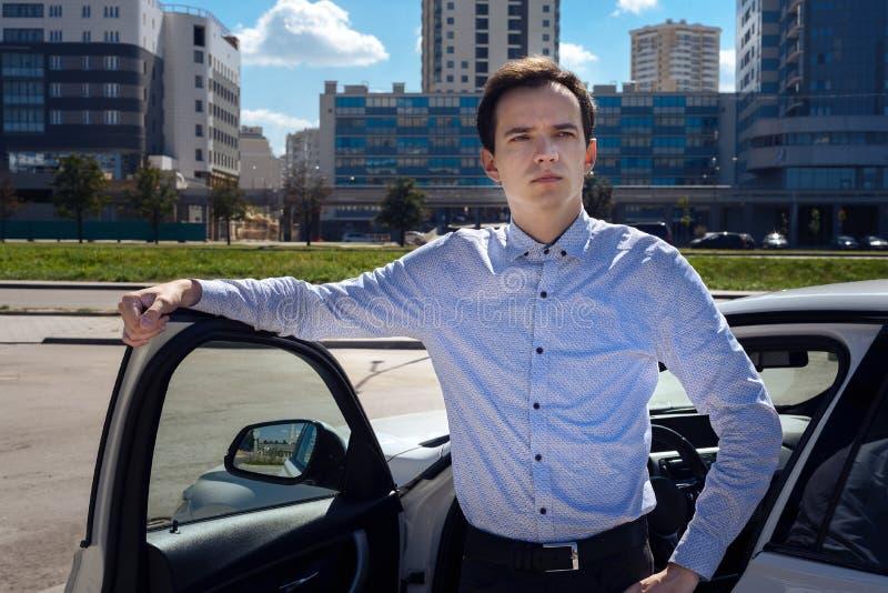 衬衣的年轻人是在汽车附近 免版税图库摄影
