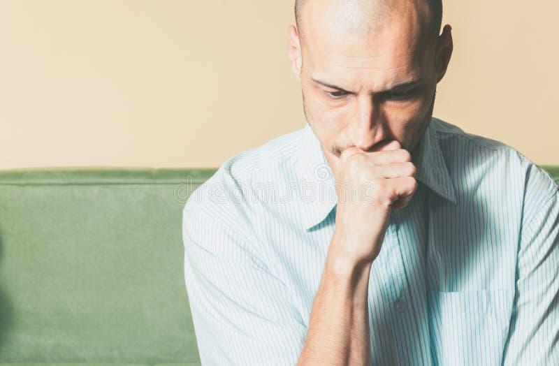 衬衣的年轻英俊的人有感到哀伤的面孔的表示的压下和凄惨,当考虑生活时的他 库存图片