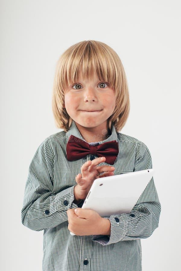 衬衣的微笑的男生有红色蝶形领结的,在白色背景中拿着片剂计算机 免版税图库摄影