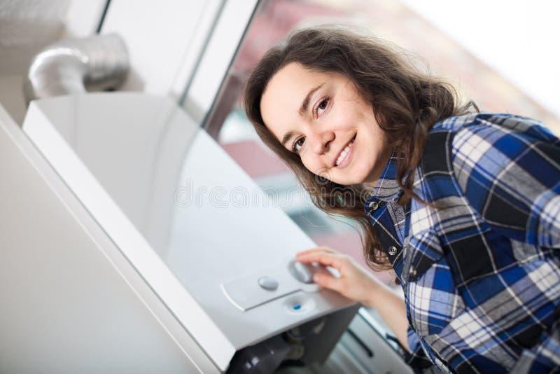 衬衣的成人女孩在锅炉控制盘区附近 库存图片