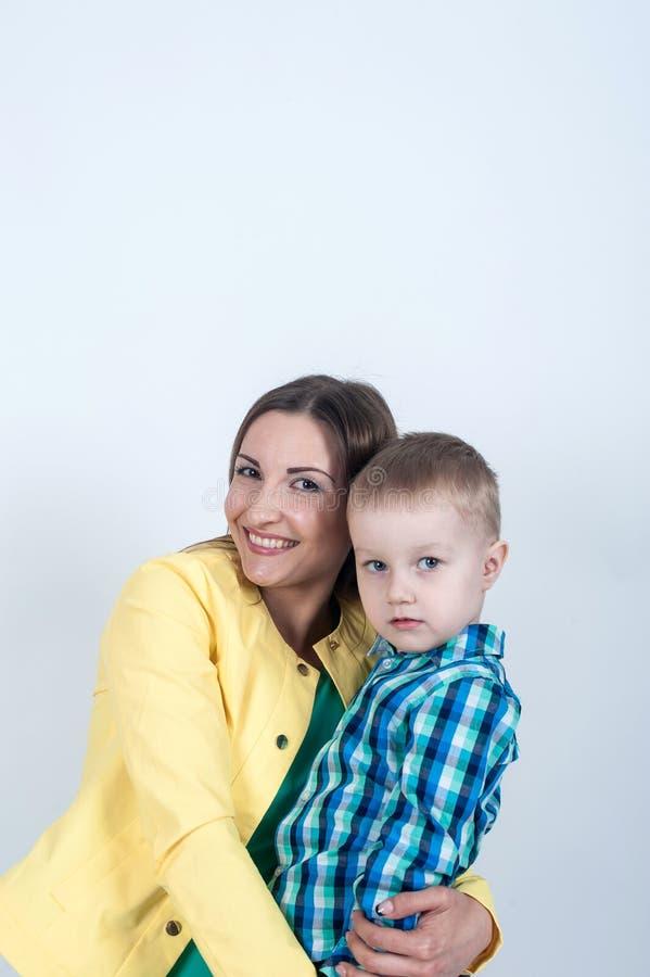 衬衣的男孩与妈妈坐轻的背景 免版税库存图片