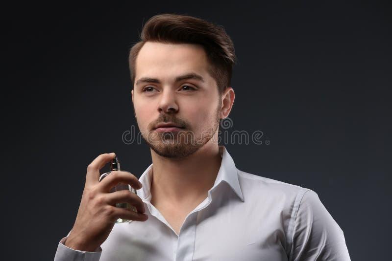 衬衣的英俊的人使用香水 免版税图库摄影
