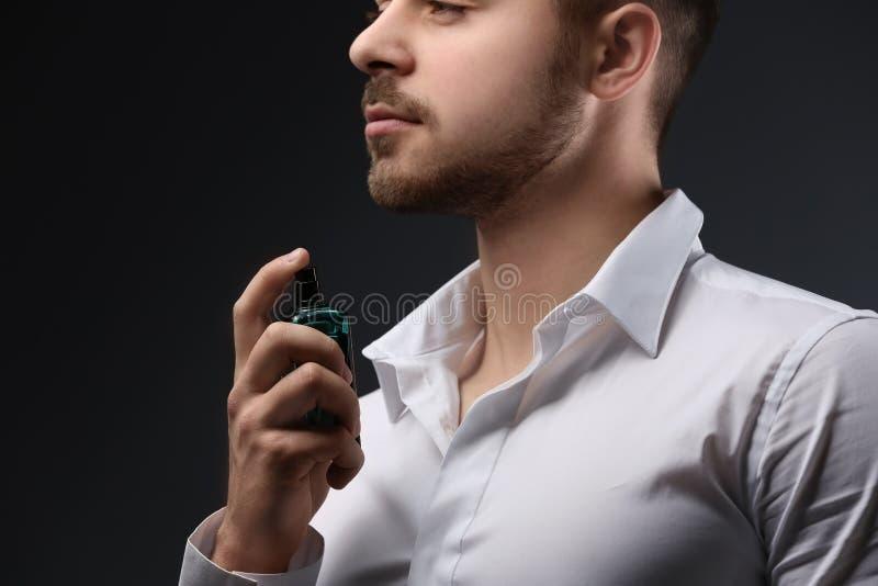 衬衣的英俊的人使用香水 库存照片