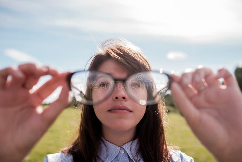 衬衣的年轻美丽的女孩有长的头发的通过玻璃看 免版税库存图片