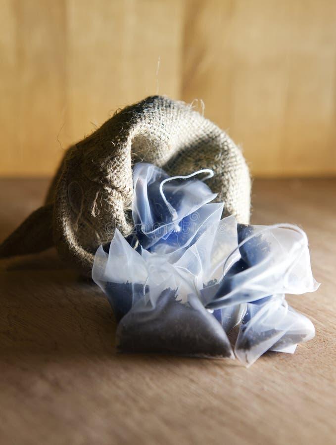 袋子在丝织物包装的精华茶在帆布在木背景请求 免版税库存图片