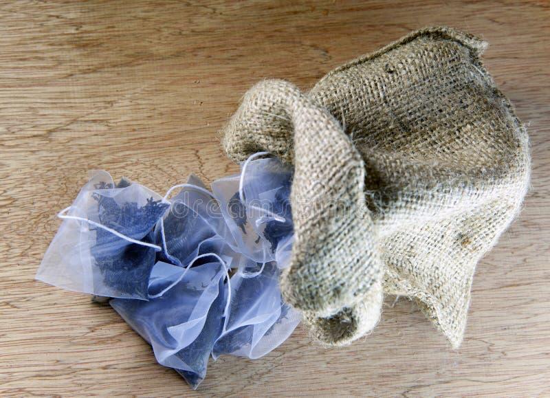袋子在丝织物包装的精华茶在帆布在木背景请求 库存照片