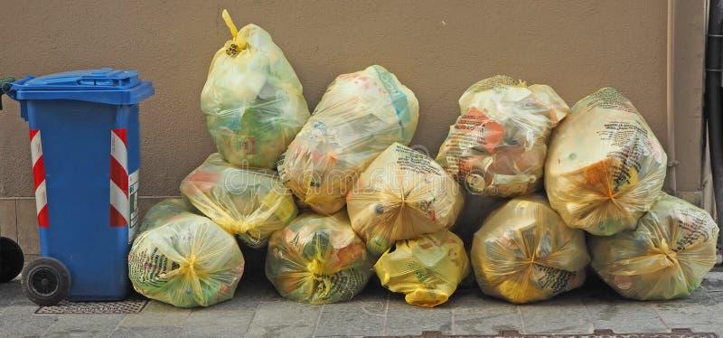 袋子在城市的街道边路的可再循环的垃圾等待收集 库存图片
