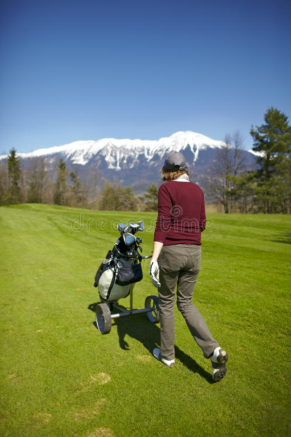 袋子打高尔夫球她推进的台车妇女 免版税库存图片