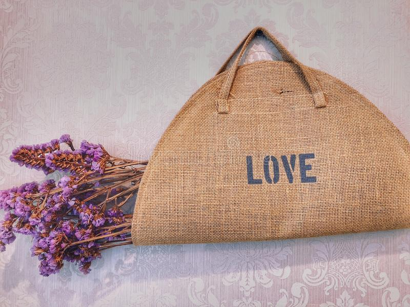 袋子爱,在棕色织品袋子的干紫色花 图库摄影