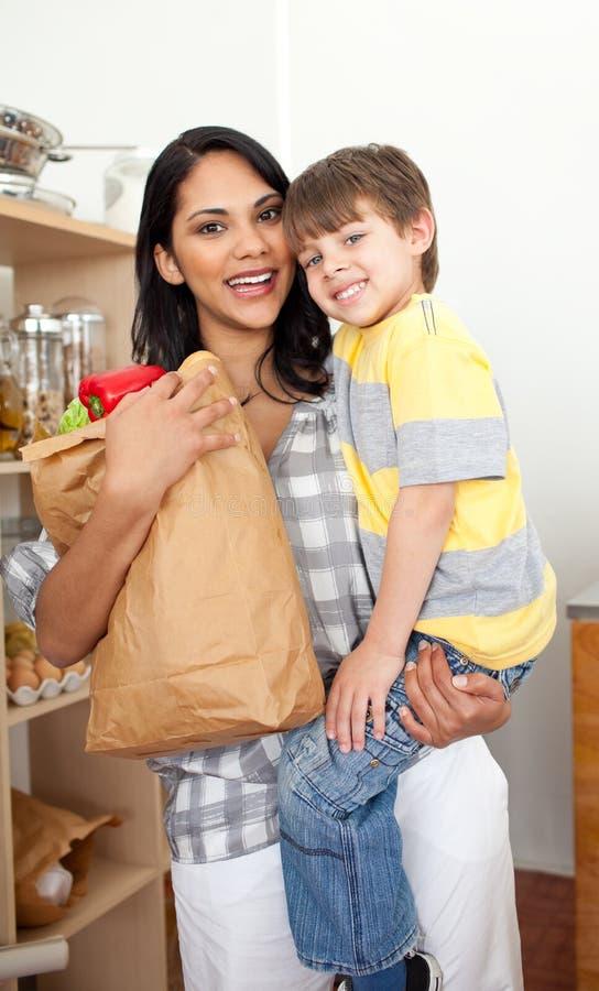 袋子男孩副食品打开他的小的母亲 免版税图库摄影
