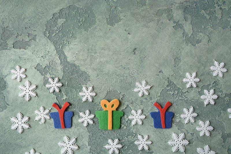 袋子看板卡圣诞节霜klaus ・圣诞老人天空 雪花和毛毡giftboxes在绿色石背景 顶视图 复制空间 平的位置 圣诞节概念 holida 库存照片