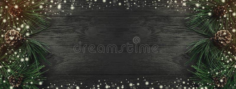 袋子看板卡圣诞节霜klaus ・圣诞老人天空 黑木背景,与杉木分支和杉木锥体从一个旁边,顶视图 Xmas长方形祝贺 库存照片
