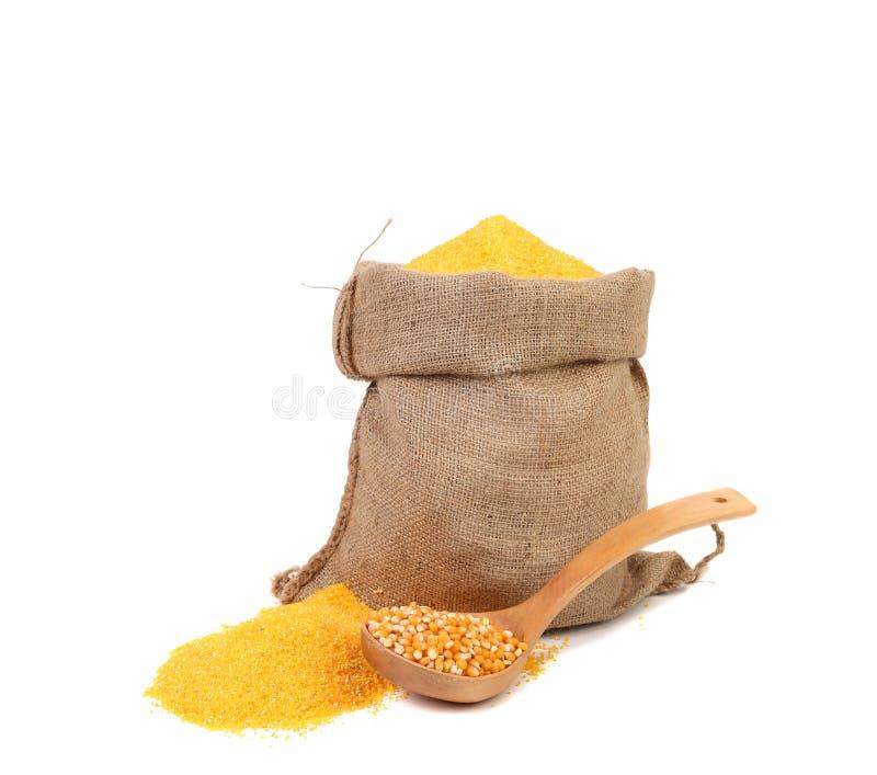 袋子碎玉米和一把木匙子。 免版税库存照片
