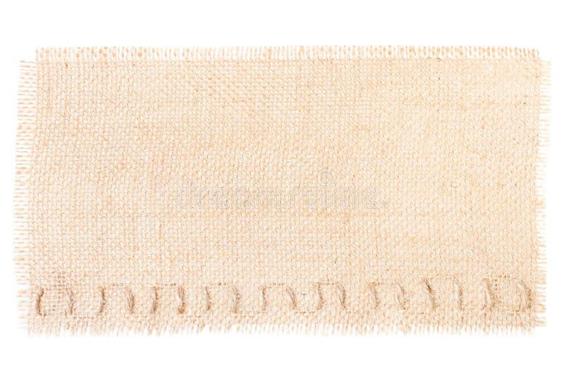 麻袋布标记装饰在白色的粗麻布纹理 图库摄影