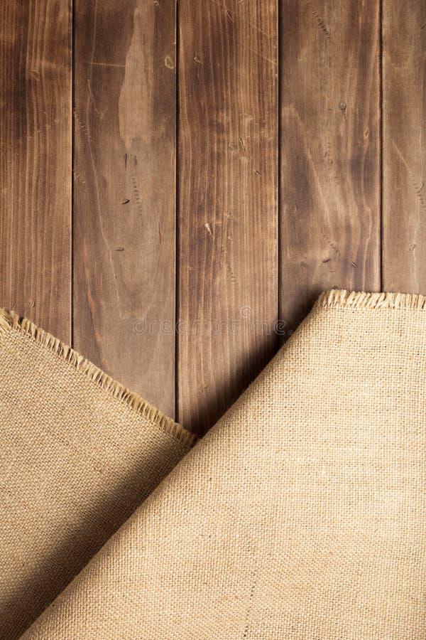 袋装在木背景桌上的粗麻布粗麻布 免版税库存图片