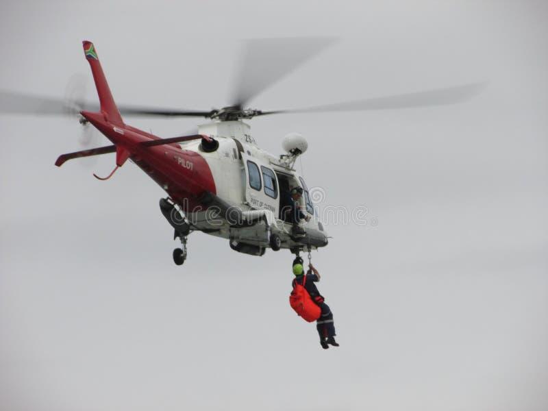 被上升入直升机的一名紧急工作者 免版税库存图片
