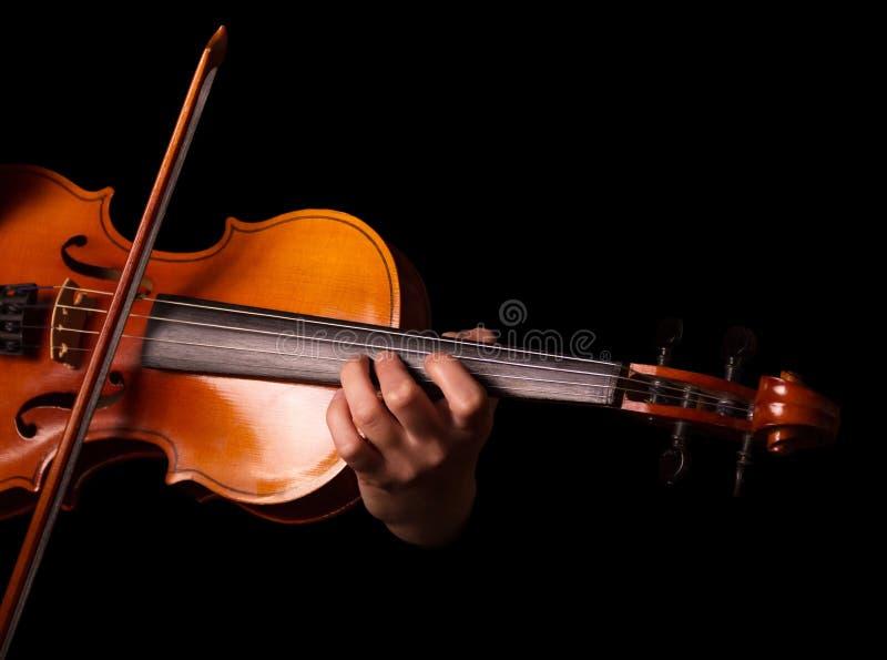 被串起的乐器,小提琴在执行者` s手上,隔绝在黑色 库存照片