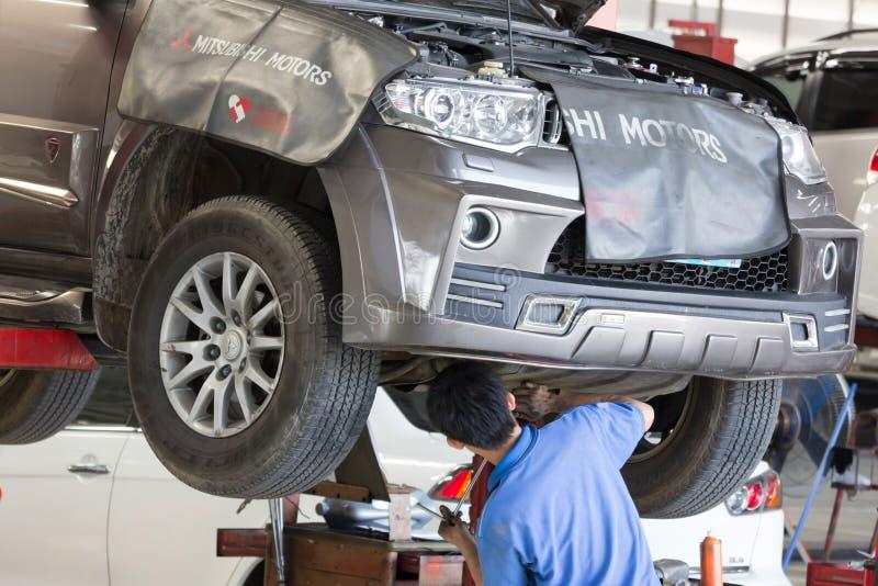 被举的汽车汽车修理工审查的汽车停止  免版税库存照片