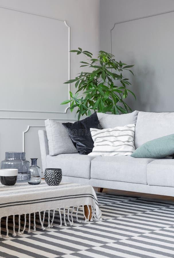 被仿造的地毯和咖啡桌与杯子和玻璃花瓶在时髦的客厅有灰色沙发的 免版税库存照片