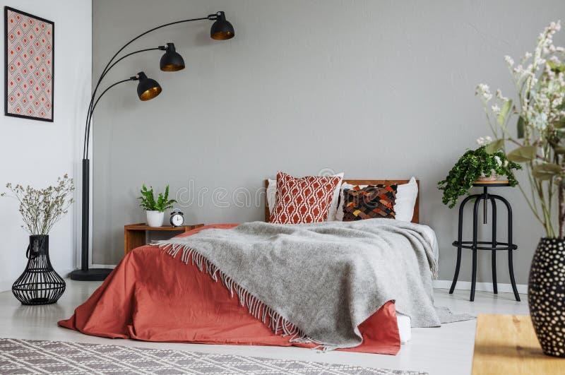 被仿造的枕头和灰色毯子在加长型的床上与深黄鸭绒垫子在豪华卧室内部在典雅的公寓 免版税库存照片
