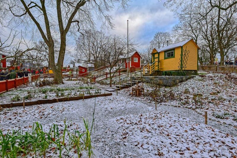 被保存的传统五颜六色的木分配地段小屋冬天视图在斯堪森博物馆建筑学灯台露天博物馆和 图库摄影