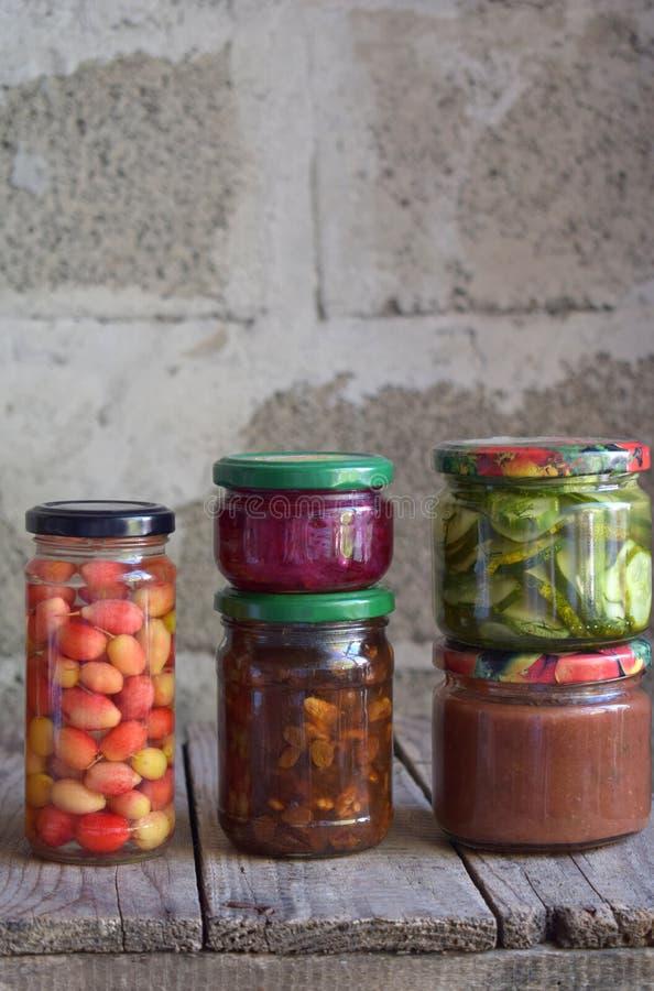 被保存的食物品种在玻璃瓶子-腌汁,果酱,橘子果酱,调味汁,番茄酱的 保存蔬菜和水果 被发酵的fo 免版税库存图片