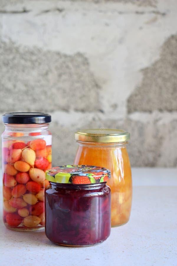 被保存的食物品种在玻璃瓶子-腌汁,果酱,橘子果酱,调味汁,番茄酱的 保存蔬菜和水果 被发酵的fo 库存照片
