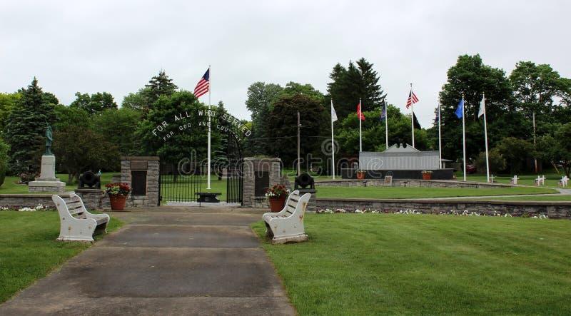 被修剪的导致十字架站立尊敬军事的纪念品,纽约中部的草坪和走道,2018年 免版税库存图片